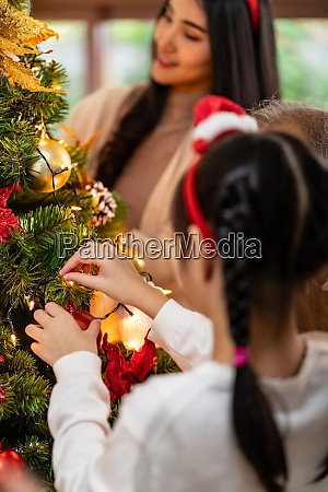 little girl decorate christmas tree with