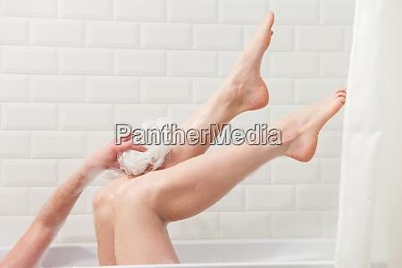 woman in bath washing leg in