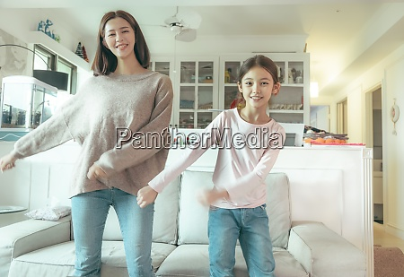 happy mother and daughter dancing at
