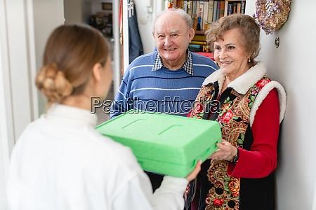 senior couple greeting volunteer delivering a