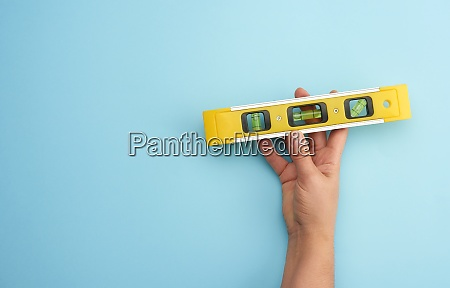 female hand hold plastic yellow level