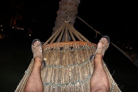 legs tourist resting in hammock at