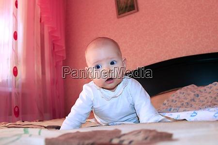 newborn baby lying on bed little