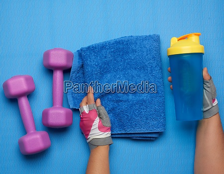 pair of dumbbells and blue towel