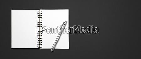 blank open spiral notebook and pen