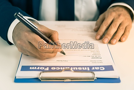 insurance agent hand writing car insurance