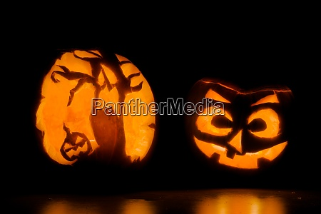 two intricately carved halloween pumpkins lit