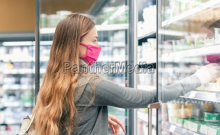 woman in supermarket shopping in dairy