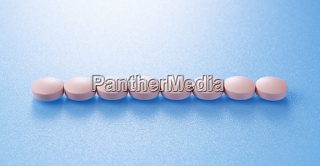 pink pills placed on blue background