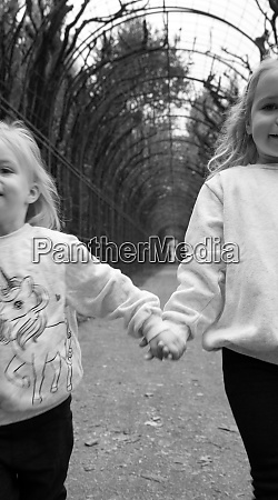 two young girls holding hands running