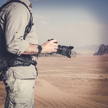 photographer holds the camera ready for