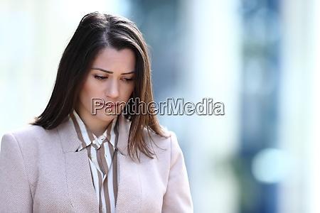 sad woman walking in the street