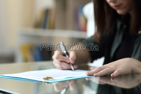 wife signing divorce document at home
