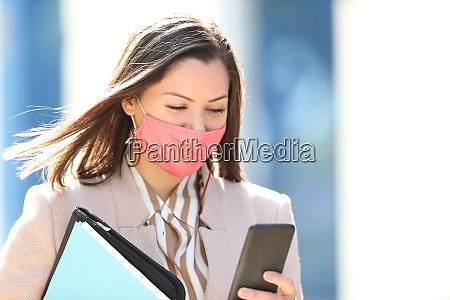 businesswoman with mask reading phone content