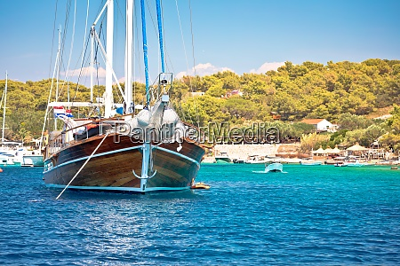 wooden sailboat in turquoise bay of