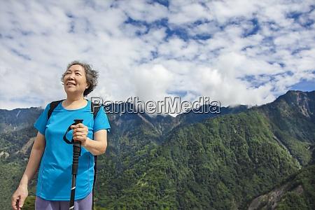 asian senior woman hiking on