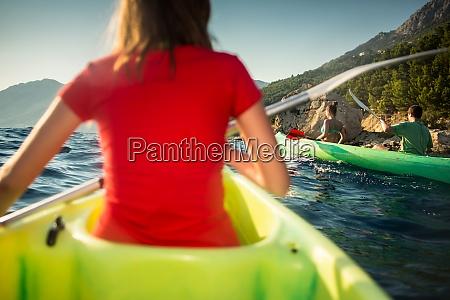 group of friends sea kayaking on