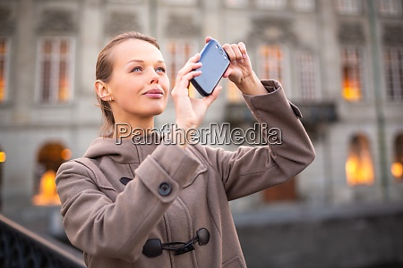 elegant young woman taking a photo