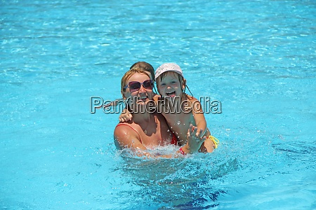 happy mother swimming with her daughter