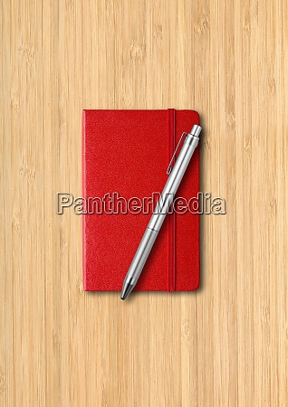 red closed notebook with a pen