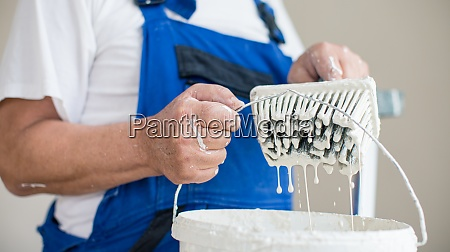 senior man painting a room of