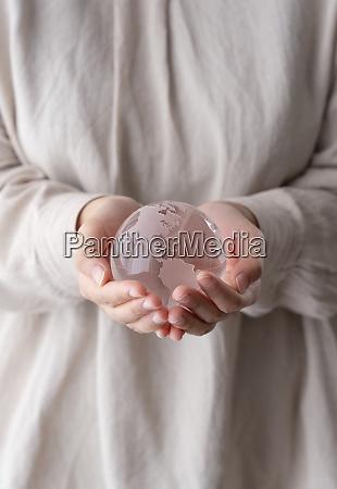 female hand with glass globe peace