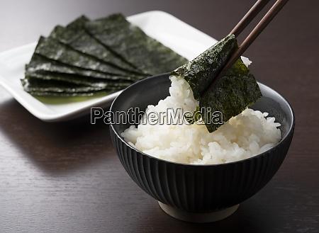 wrapping nori around rice set against
