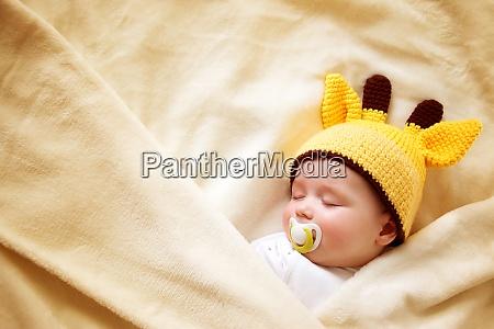 baby sleeping in giraffe hat