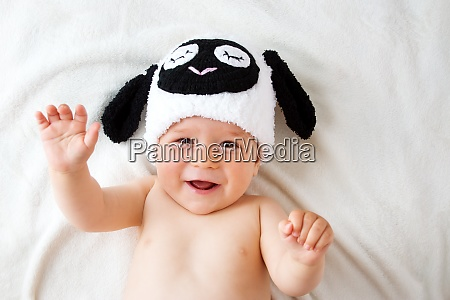 baby in a sheep hat lying
