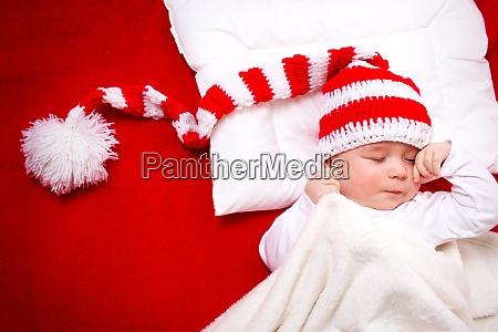 sleepy baby on red blanket
