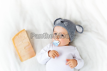 baby boy in mouse hat lying