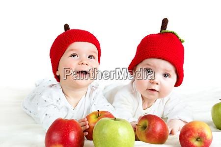 two cute babies lying in hats