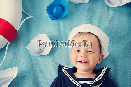 boy playing with paper ships