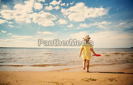 boy walking at sea in straw