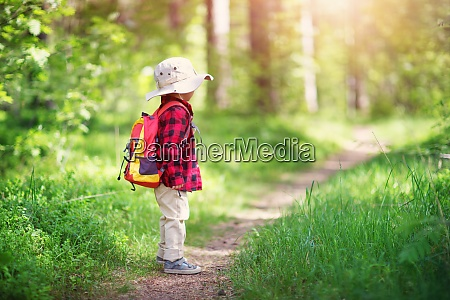 boy going camping with backpack in