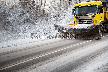 truck cleaning on winter road covered