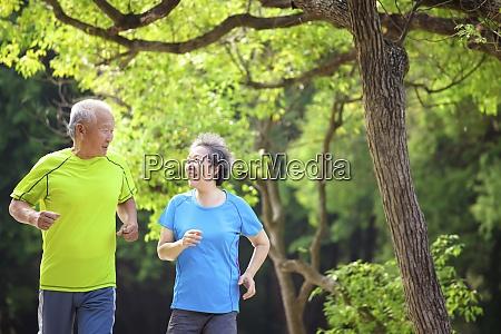 happy senior couple jogging in