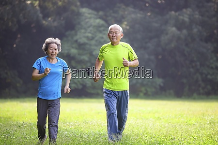 asian senior couple jogging in