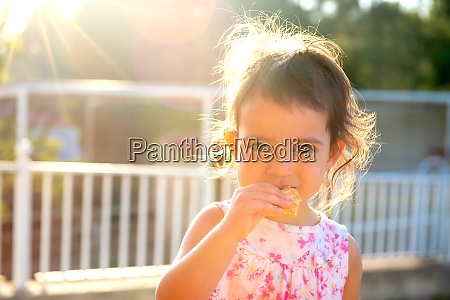 toddler at sunset eating a cookie