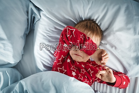 sleepy boy lying in bed with