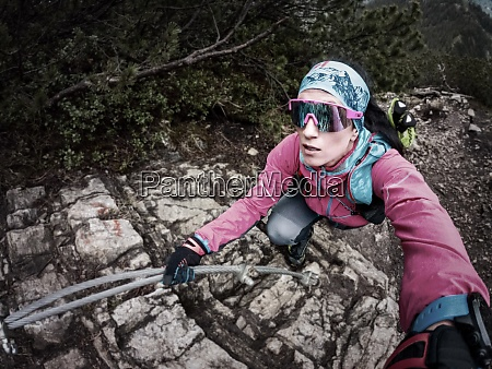 trail runner climbs up via ferrata