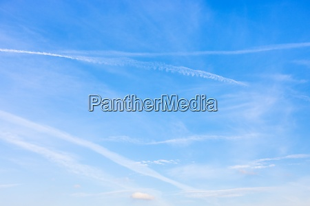 several contrails and cirrus clouds in