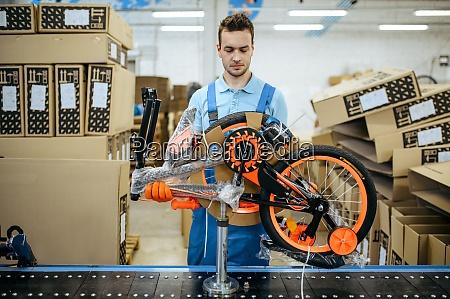 bicycle factory worker packs teen bike
