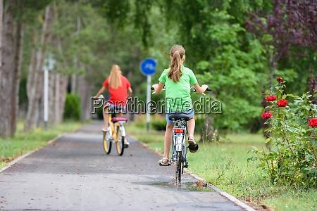 two girlfriends ride a bike along
