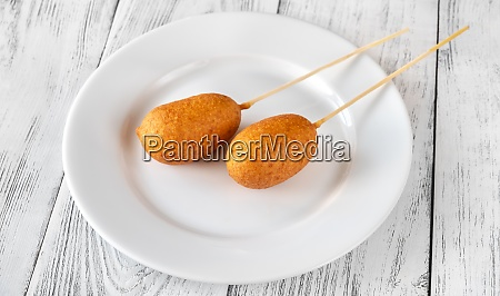 corn dogs on white plate