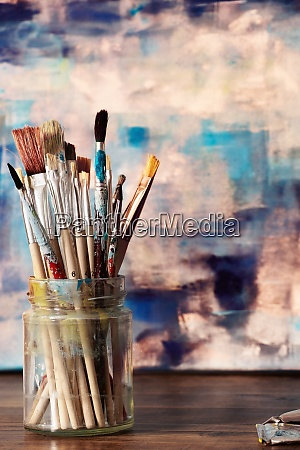 paint brushes and abstract artwork on