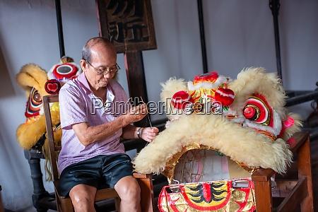 a man sew the lion dance