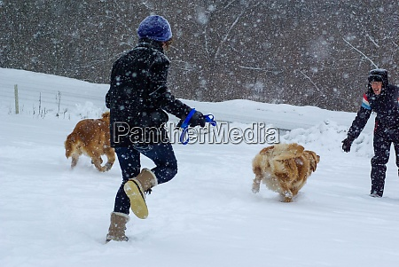 two people run with happy dogs