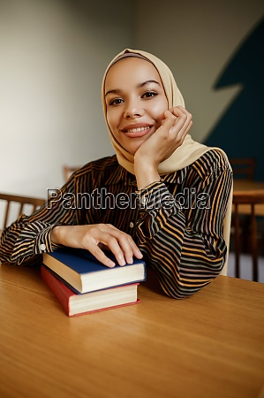 arab female student in hijab holds