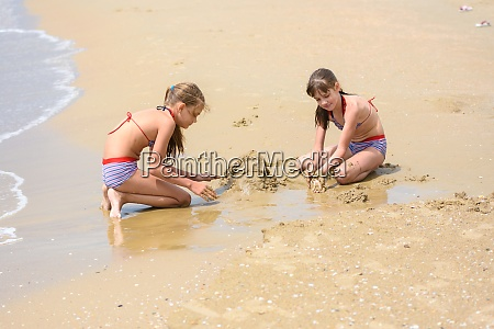 two girls build sand castles on